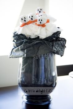 This little Halloween craft turned out super cute. And it was so easy to do. What you will need: Lollypops White crepe paper {it's a little easier than tissue paper} or you can also use paper towel Ribbon Black pen Vase Black tissue or crepe paper Styrofoam block, florist foam or pebbles Let get started! Make your little ghosts by wrapping some crepe paper over the top and tying a ribbon around the base of the lollipop, making a 'neck'. Draw a face with black marker.  Place tissue or crepe…