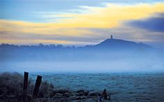 Glastonbury Tor rises out of the Somerset Levels, home once again to the large blue butterfly Glastonbury Somerset, Glastonbury Tor, Die Nebel Von Avalon, Wells Somerset, Somerset Levels, Mists Of Avalon, Celtic Mythology, Dark Forest, Blue Butterfly