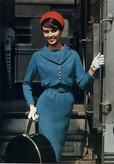 a model getting off a bus in the late Sixties wearing a blue suit with a cropped jacket and narrow skirt