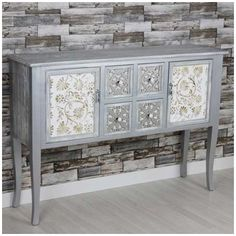 Mueble recibidor de madera plata blanco con tallados marrones y plateados de 4 cajones y 2 puertas.