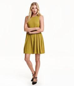 Verde aceituna. Vestido de línea en A en punto. Sin mangas, con sisas amplias, capa doble en la parte superior y bolsillos en las costuras laterales.