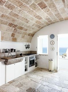 Mediterranean Kitchen with Limestone, Flush, High ceiling, Farmhouse Sink, Step On Metal Round Waste Can by Brewer, Shutters