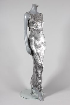 A Paco Rabanne chain-mail sheath, the knitted cotton mesh ground inter-looped with silver metal discs giving an over-lapping fish-scale effect, with a demi-lune panel to the front bodice, figure hugging skirt with fish-tail hem Metal Fashion, 70s Fashion, Fashion History, Leather Fashion, Fashion Brands, Fashion Beauty, Vintage Fashion, Fashion Outfits, Paco Rabanne