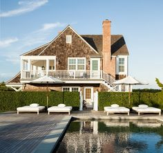 stunning cape cod home with wood deck surrounding pool