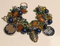 Handmade Notre Dame Charm Bracelet: Chunky Cluster Bracelet with various Navy, Gold, and Green beads and two Notre Dame Charms by RoyalStreetBoutique on Etsy