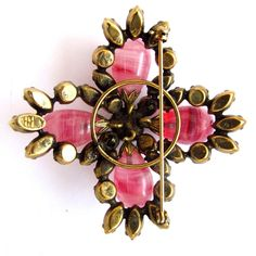 This gorgeous signed Regency brooch features swirled pink art glass cabochons surrounded by vivid pink marquise rhinestones and aurora borealis pink