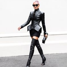 All black leather outfit street style fashions.  Modern cut leather jacket with flared bottom, black stretch knit skirt, above-the-knee leather boots with open toe, dark sunglasses, and matching clutch.
