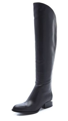 A gravity-defying sliced heel cuts a unique silhouette for these leather Alexander Wang boots. Running down from an asymmetrical top line, the long back zip shines with the same polish as the plate in the cutout, stacked heel. Leather sole.