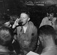 """USN pilots in the ready room of USS Monterey, on June 20, 1944 — the message emblazoned on the chalkboard behind is clear and simple: """"Get the Carriers"""". The pilots were so successful in this task during the campaign that it's been referred to as the """"Great Marianas Turkey Shoot"""""""