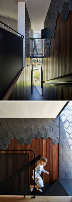 Exterior siding materials like grey slate tiles and wood flow through to the interior of this modern house and the stairs leading to the upper floor.