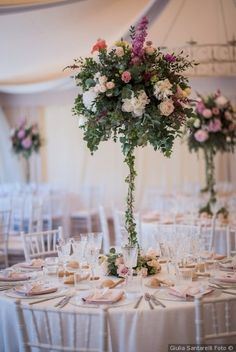 Centrotavola di matrimonio alto con piante e fiori per tavoli rotondi. Centrotavola con colori pastello