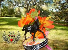 ♥ KENTUCKY SUNRISE was made in the spirit of the Kentucky Derby, but with a different flower...the hibiscus. Why not? Its beautiful! ♥ This fascinator is round and flat, and is secured onto a solid, pink headband ♥ The winning black horse pops out against the fiery orange and yellows of the hibiscus flowers which surrounds the horse ♥ Along for the ride, there are two butterflies, one orange, one pink, on the back of this fascinator ♥ White polka dots on black ribbon circle the circumference…