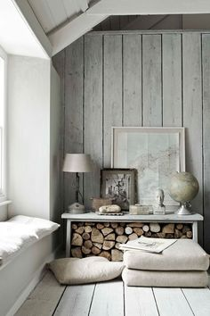 This room has a very neutral palette with wooden walls and rustic style logs under the table.