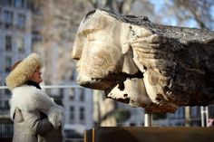 "British sculptor Emily Young poses for a photograph with a large stone head she created in Berkeley Square on February 2, 2012 in London, England. The head will form part of an installation of six stone heads entitled ""Metaphysics of Stone"" which will be on public display in Berkeley Square from February 7, 2012 until April 25, 2012."