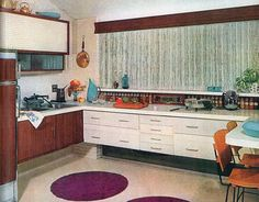 """A spruced-up, tiny prefab on a narrow lot was the home of this little kitchen in 1961. The kitchen gave the impression of being much bigger, according to House Beautiful's editors. """"One important reason is that the cabinets have been raised so that the eye sees the continuation of the floor to the back wall,"""" they wrote. The kitchen had an oven, but no surface cooking units — only """"portable, thermostatically controlled appliances stored in large drawers and brought out for use."""""""