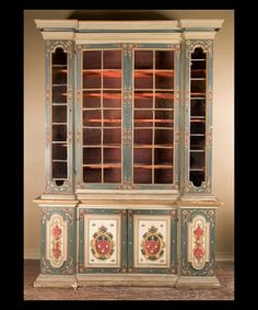 Italian century cabinet beautifully painted in the century from Bologna with 4 doors on bottom and 4 doors on top and has original glass doors that are painted with Heraldic design