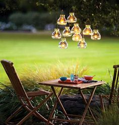 Create romantic lighting for an outdoor dinner party by suspending votives (we used mini recycled-glass tea light lanterns) at varying heights from low-hanging branches.