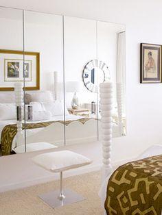 En este dormitorio predomina el blanco, sin concesiones, color que multiplica la luz, al igual que los frentes de armario revestidos de espejos. En ellos se refleja la cama, con una singular estructura de madera tallada esmaltada en blanco y vestida con una manta étnica en colores tierra. Un espejo redondo devuelve lo reflejado en el armario, consiguiendo un calidoscópico efecto