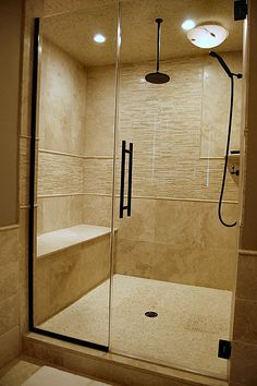 Contemporary Master Bathroom - Neutral travertine tile, oil rubbed bronze fixtures, frameless shower, built in bench