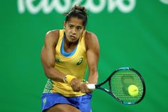 Teliana Pereira of Brazil plays a backhand against Caroline Garcia of France in their first round match on Day 2 of the Rio 2016 Olympic Games at the Olympic Tennis Centre on August 7, 2016 in Rio de Janeiro, Brazil.