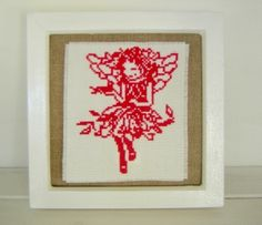White painted wood frame which can be hung onto a wall or placed onto a flat surface. Hand stitched cross stitch fairy with bird embroidery which has been mounted onto vintage cotton fabric. Glass cover.  Measurements approx 7.5 x 7.5 inches (20cm x 20cm)