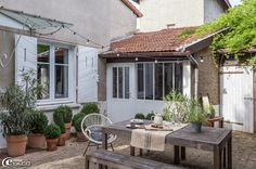 Chez Florence Bouvier, la terrasse devant la maison est éclairée par une guirlande lumineuse 'Un Esprit en Plus'. Fauteuil en rotin chiné au...