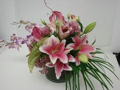 This is a floral arrangement that features lilies, miniature calla lilies and dendrobium orchids in a pink color scheme. See our entire selection at www.starflor.com.  To purchase any of our floral selections, as gifts or décor, please call us at 800.520.8999 or visit our e-commerce portal at www.Starbrightnyc.com. This composition of flowers is generally available for same day delivery in New York City (NYC).  LV025