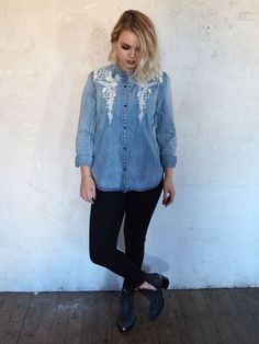 Denim button up shirt with snap buttons and floral embroidered detailing. Curved hem.