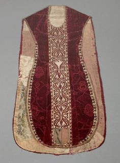 Chasuble Date: ca. 16th century Country: Italy Accession Number: 1982.14.1 Dark red silk voided velvet in pomegranate ferronerie design. Orphrey of white silk cut velvet appliqued with red silk velet in s-shaped ribbons held together at the center. Heraldic shields at the bases of the orphrey, front and back. Possibly from a private chapel. Original inventory lists this as 18th century, but many of the bits are older.