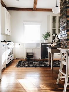 Exposed wood beams, wood floors, exposed brick, white cuboards, hamptons style kitchen with persian rug.
