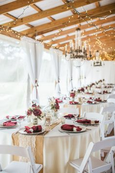 Rustic Barn Wedding Reception with String LIghts, Chandeliers, Burlap and Lace Runners on Cream Linen with Burgundy Napkins and Red Rose Centerpieces in Mason Jars with White Folding Chairs