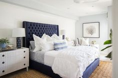 A dark blue tufted wingback bed with a silver trim is complemented with white and blue bedding and sits on a seagrass rug between light gray nightstands topped with dark blue medallion lamps. Blue Headboard, Blue Bedding, Headboard Ideas, Bedding Sets, Wingback Bed, Tufted Bed, Tufted Headboards, Blue Master Bedroom, Gold Bedroom
