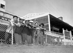 Gathering on a fence are some of the first Japanese to be removed from American society and sent to the Tanforan internment camp in Tanforan, California. The group was among the 3,112 Japanese to be removed from restricted areas in the San Francisco Bay area.