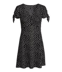 Black/dotted. Short dress in airy, crêped viscose fabric with a printed pattern. V-neck at front with decorative buttons, short sleeves with knot detail,