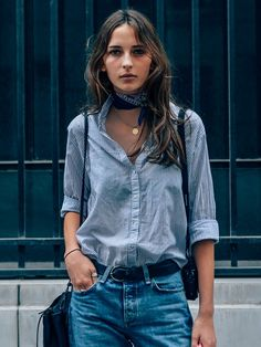 A striped button-down is worn with a bandana, gold necklace, and belted jeans