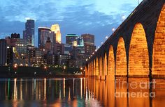 Minneapolis Skyline Photography  The Stone Arch Bridge is a classic symbol of Minneapolis. It is a view of an era gone by, mixed with the modern. The bridge built by a great railroad baron, was used to create much of the wealth of the region being the means by which grain could come to market in the breadbasket of the country. This image is one of Wayne's most popular, being used for book covers, marketing material for local corporations and art on many fine homes.