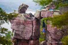 """Hang in there!  Climber having a bit of fun at Devil's Lake State Park's famous """"Devil's Doorway"""" rock formation - www.devilslakewisconsin.com"""