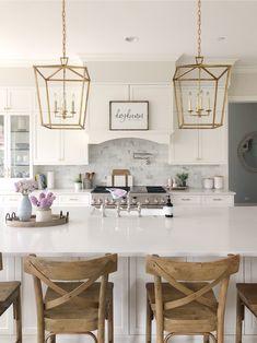 Pretty and fresh spring kitchen features brass lanterns, wood stools, white cabinets, white quartz counters, and pretty spring flowers #kitchendesign #kitchenideas #kitchendecor