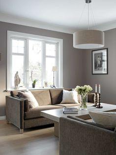 Stuen er preget av rene linjer og duse toner. Med grått som grunnfargen har eierne valgt å kombinere dette med fargetoner som beveger seg fra hvitt til mørk brun.
