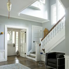 Blue Gray Foyer with White trim, Wood floors, Wood steps and White Risers