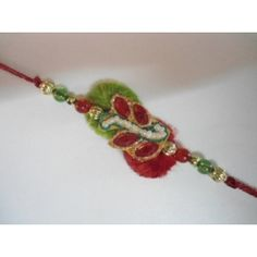 The center of the rakhi has pearl and surronded by red stones, gives it a beautiful leaf look. red stones  are further surrounded by golden swirl Zari work. This rakhi has two colour base Green and red.
