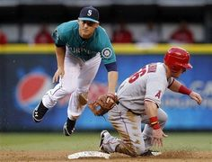 Game #47 5/25/12: Seattle Mariners second baseman Kyle Seager, left, jumps out of the way as Los Angeles Angels' Kole Calhoun slides into second base in the third inning in a baseball game Friday, May 25, 2012, in Seattle. Calhoun and John Hester were out on the double play. (AP Photo/Elaine Thompson)