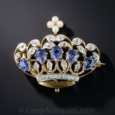Coronate yourself or your loved one with this stunning Edwardian era crown brooch, hand-fabricated in platinum over gold during the first or second decade of the twentieth century, A quintet of faceted pear shape sapphires, totaling 2.00 carats, are enveloped by small sparkling white European-cut diamonds, topped with a lustrous seed pearl finial. Fit for a queen, or at the very least a princess. 1 1/4 by 1 inch.