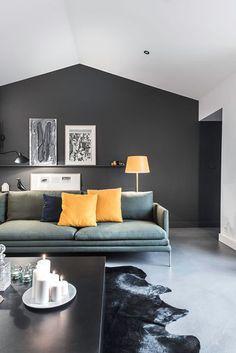 Le salon ose la peinture noire mais l'accompagne d'un canapé italien et de touches de couleur jaune pour égailler. Plus de photos sur Côté Maison http://petitlien.fr/83en