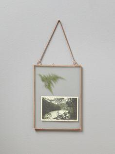 Cadre photo vintage finement bordé de métal doré et suspendu par une…