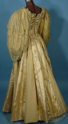 "c. 1890's Mme. Elise, Boston, USA Beaded Yellow Silk Brocade Ball Gown with Huge Chiffon Balloon Sleeves! A brilliant yellow floral and striped silk brocade interspersed with a yellow grosgrain material and silk ribbons with bows. The bodice is beaded on the front in a faux ""vest"" design.  The sleeves are massive balloon with swags of silk crepe chiffon"