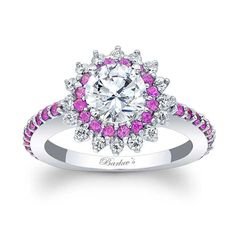 This unique starburst halo engagement ring features a prong set round diamond center encircled with pink sapphires and  diamonds set in a starburst pattern. The dainty shank is adorned with shared prong set pink sapphires running down the shoulders for an elegant finish.