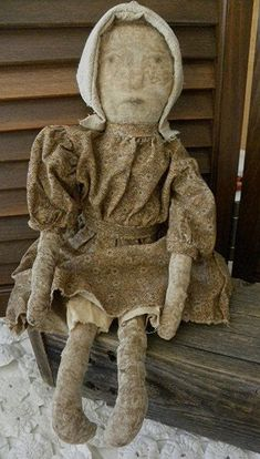 This 19 tall very worn, aged, early americana era style doll is reminescent of a doll from centuries ago. She wears an old fashioned dress made from dark gold/mustard print with waistband ties in the back. Her bloomer underpants were made from vintage muslin. Please note that the fabrics