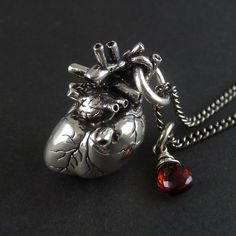 "Anatomical Heart Necklace with Sterling Silver Wire Wrapped Garnet - Antique Silver Anatomical Heart Pendant on 24"" Gunmetal Chain. $80.00, via Etsy."