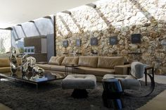 Interior, Captivating Living Room Rough Stone Walls Design Ideas With Cream Puffy Leather Sofa And Grey Fur Rug Without Unique Single Grey Puffy Sofa: Awesome Natural Stone Movement for Natural Home Interior Design Ideas
